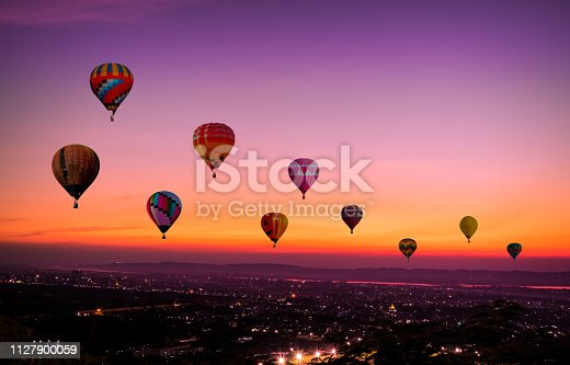 The Colorful hot air Balloons  flying above city on sunset time before dark coming with colorful of light and a beautiful twilight and sunset sky background.