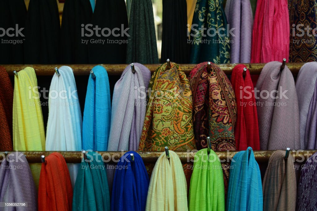 the colorful scarf hang on metal bar at the local store of...