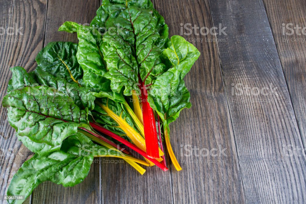 The colorful stems of Chard on dark wooden table. stock photo