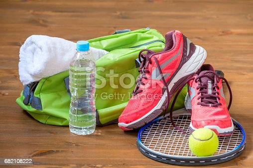 istock the composition of sports facilities on the dark wooden floor with a rocket for tennis 682108222