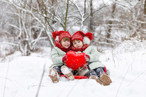 Girl twins are sitting on the snowy ground and holding together a bright red heart in their hands.The concept is St. Valentine's Day