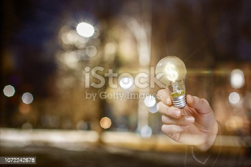A lightbulb with a currency unit inside is in businessman's hand at the bright night city background. The concept is the financial efficiency of innovative idea.