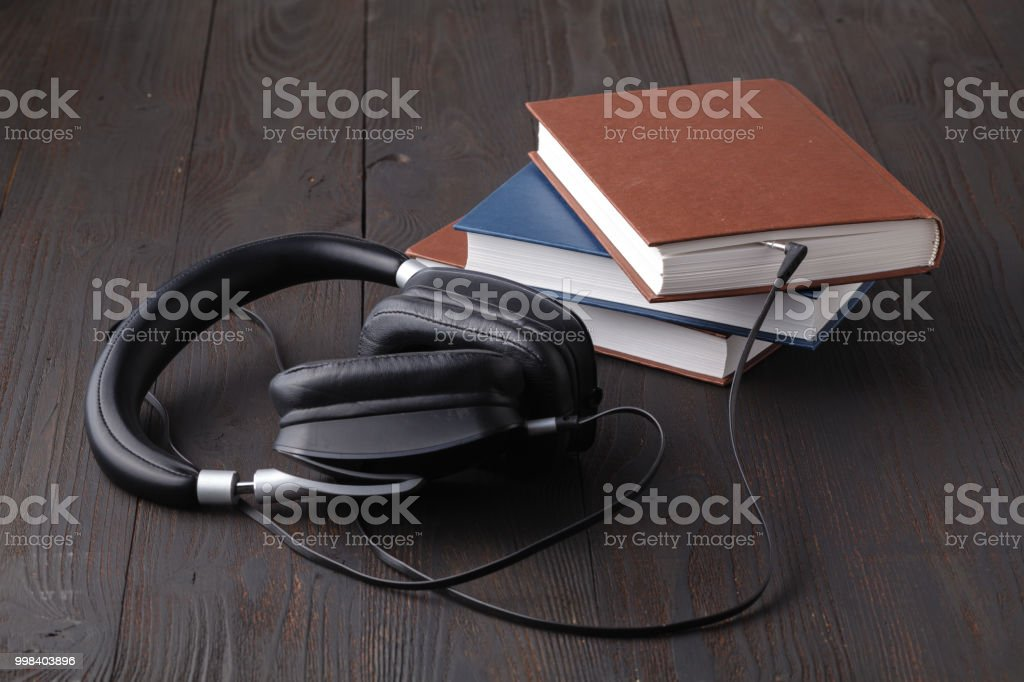 The concept is to listen to audiobooks. headphones are connected to the book stock photo