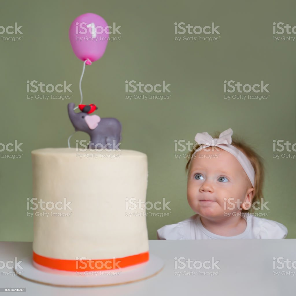 Baby girl looking on birthday stollen cake. Positive emotions on the...