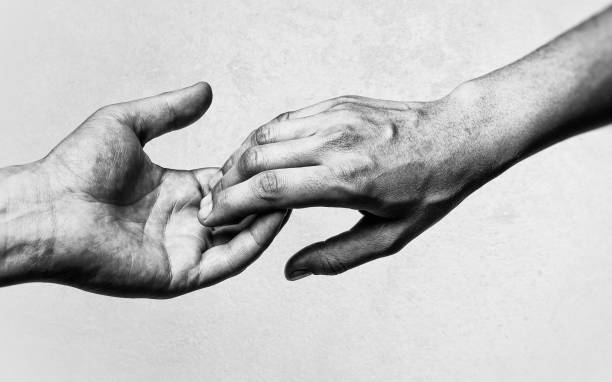 The concept of breaking relations. Emotional, black and white photo of two hands at the moment of farewell. The concept of breaking relations. deportation stock pictures, royalty-free photos & images