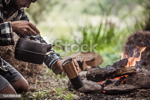istock the concept of camping the guy on the nature of the fire 1042695458