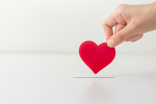The concept of charity, love, donate and helping hand. Woman's hand places heart in the donation slot. Donor of blood or human organs, saving lives.