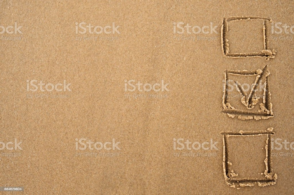 The concept of choice. A tick in the questionnaire drawn on the sand. stock photo