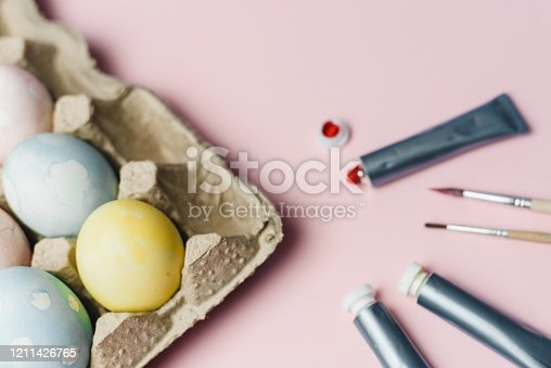 922843504 istock photo The concept of coloring Easter eggs in pastel watercolor colors. Paints and brushes for coloring eggs for Easter on pink background 1211426765