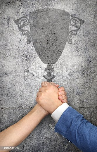istock The concept of competition. Fighting hands cast a shadow in the form of a prize cup. 933454274