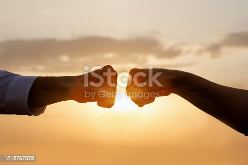 The concept of cooperation and teamwork in business. Two fists of businessmen on a background of the sun.