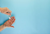 istock The concept of coronavirus COVID-19, How to protect yourself from infection. Hand means for disinfection squeeze a gel, mask and pills on the hand. Flat lay on a blue background 1213491304