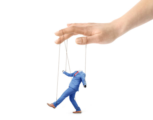 The concept of corporate slavery. A hand controls a worker on a white background. Submission of will. Puppet master. The concept of corporate slavery. A hand controls a worker on a white background. Submission of will. Puppet master. puppet stock pictures, royalty-free photos & images