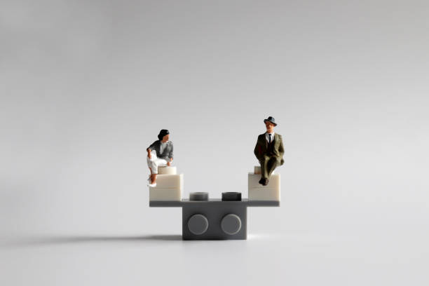 The concept of equality of opportunity for men and women. A miniature man and woman sitting on a mini seesaw. The concept of equality of opportunity for men and women. A miniature man and woman sitting on a mini seesaw. military recruit stock pictures, royalty-free photos & images
