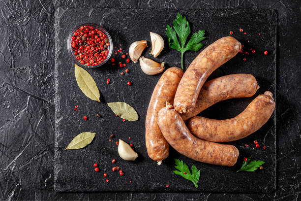 The concept of farm, organic products. Raw homemade pork barbecue sausages on a black slate board. background image. copy space