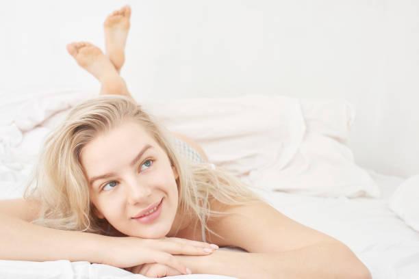 Das Konzept der weiblichen Gesundheit. Schöne lächelnde junge Frau mit einem verträumten Gesichtsausdruck liegt auf einem weißen Bett mit Unterwäsche – Foto