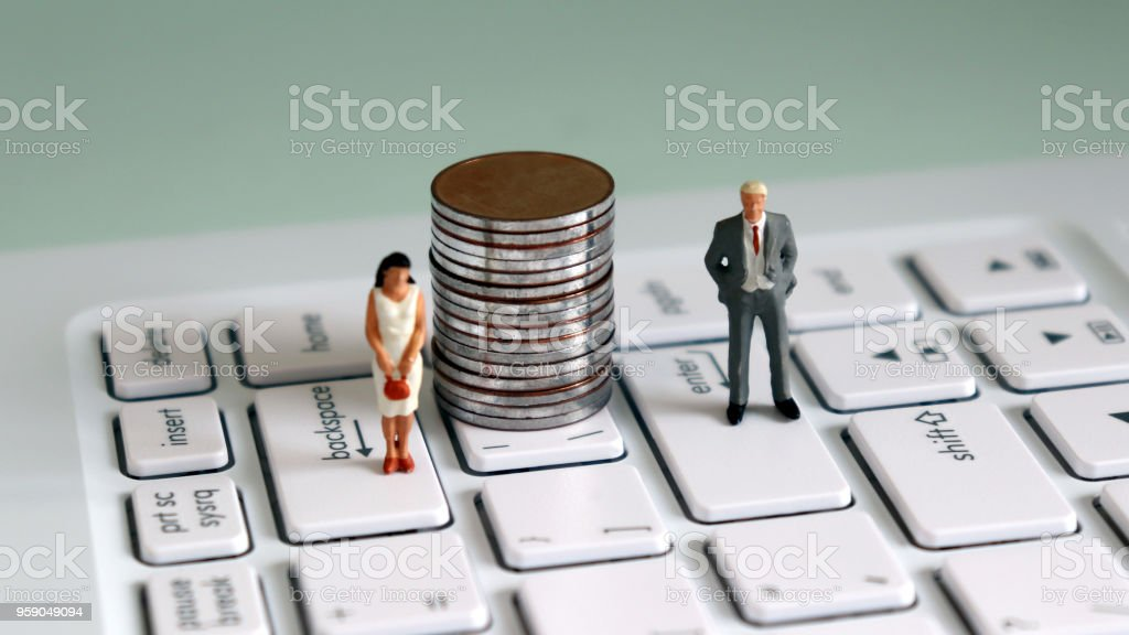 Aminiaturemanandaminiaturewomanstandingontopofthekeyboardwithapileofcoinsinthemiddle. The concept of gender unequal employment opportunities. stock photo