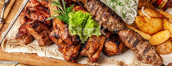 istock The concept of Georgian cuisine. Meat board with shashlik, grilled pork ribs, lulya kebab and shish kebab. Grilled french fries and grilled vegetables. Meat feed on a wooden board. Banner 1084962472