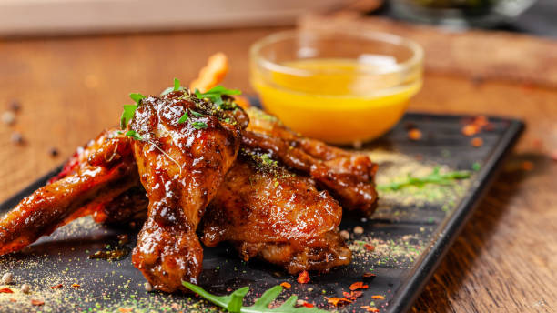 the concept of indian cuisine. baked chicken wings and legs in honey mustard sauce. serving dishes in the restaurant on a black plate. indian spices on a wooden table. background image. - musztarda zdjęcia i obrazy z banku zdjęć