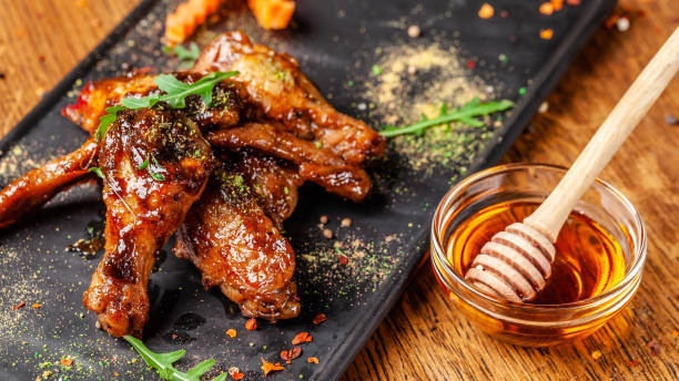 The concept of Indian cuisine. Baked chicken wings and legs in honey mustard sauce. Serving dishes in the restaurant on a black plate. Indian spices on a wooden table. background image. The concept of Indian cuisine. Baked chicken wings and legs in honey mustard sauce. Serving dishes in the restaurant on a black plate. Indian spices on a wooden table. background image. drumstick stock pictures, royalty-free photos & images