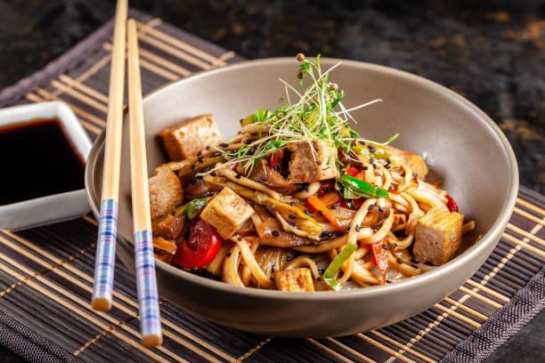 het concept van de japanse keuken. chinese noedels met kip, gegrilde groenten en tofu in unagi saus. waar aziatische gerechten worden geserveerd in het restaurant van een plaat op een bamboe mat. bovenaanzicht, kopie ruimte - sobanoedels stockfoto's en -beelden