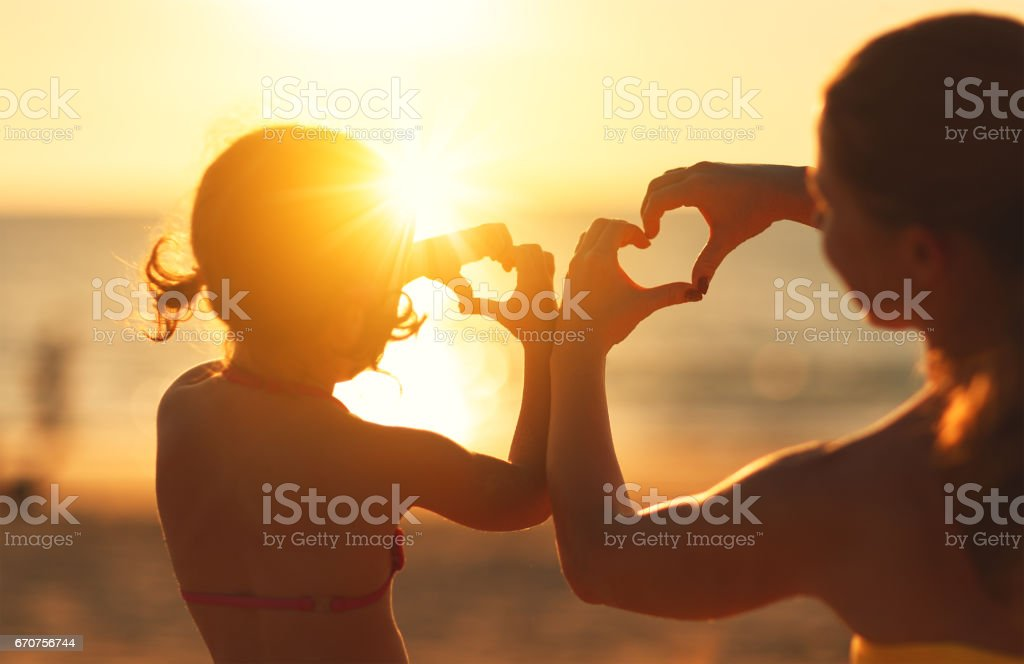 The concept of love, parenthood and happy family. Mother and child daughter show heart from hands at sunset stock photo