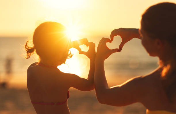 The concept of love, parenthood and happy family. Mother and child daughter show heart from hands at sunset - foto stock