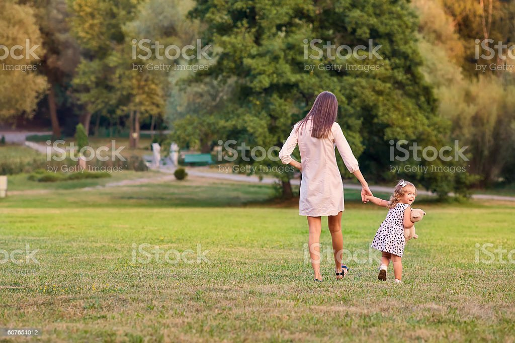 The concept of Mother's Day. Mother with little daughter walking stock photo