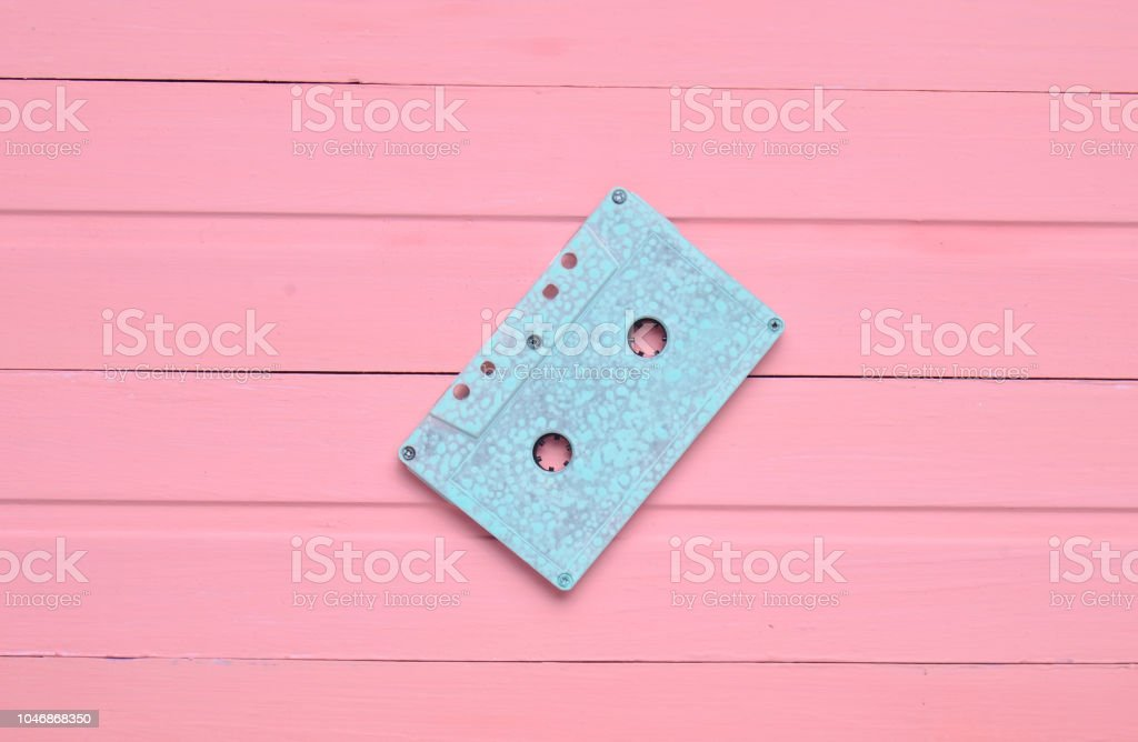 The concept of obsolete audio technology. Retro audio cassette on a pink pastel wooden background. Trend of minimalism. Top view. – zdjęcie