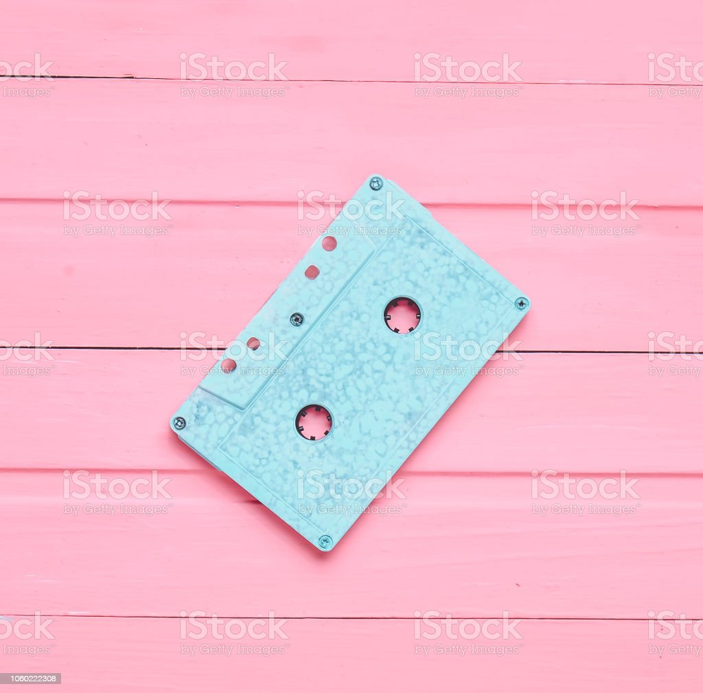 The concept of obsolete audio technology. Retro audio cassette on a pink pastel wooden background. Trend of minimalism. Top view – zdjęcie