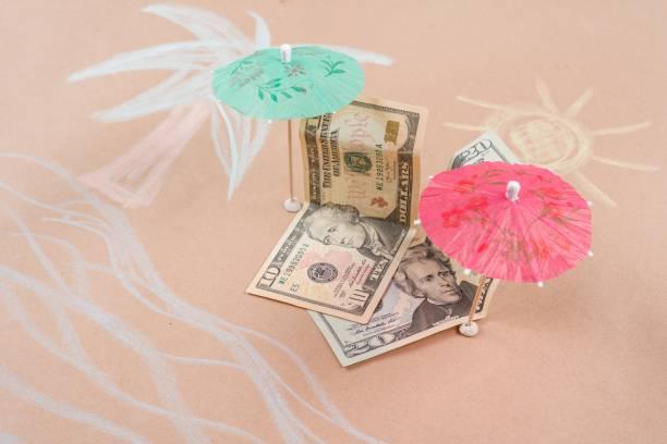 das konzept der offshore-banking und steueroasen. bild mit dollarnoten an einem tropischen strand unter einer palme und ein regenschirm - rettungsinsel stock-fotos und bilder
