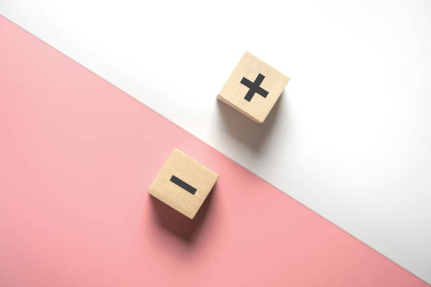 The concept of opposites, wood blog with plus and minus on white and pink background. The concept of opposites, wood blog with plus and minus on white and pink background, flat lay, copy space, top view. minus sign stock pictures, royalty-free photos & images