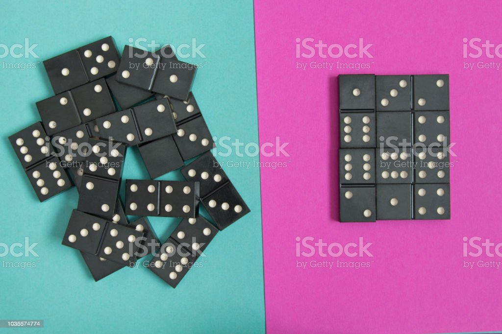The concept of order and chaos. Chaotic disorganized dominoes and ordered dominoes on colored cardboard background - fotografia de stock