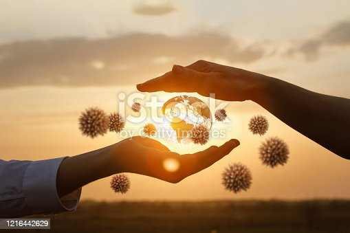 The concept of protecting the world from coronavirus.Hands protects the globe from viruses against the backdrop of a sunny sunset.