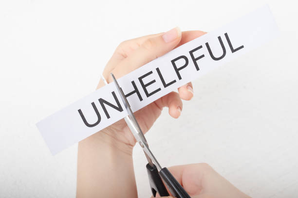 The concept of self-confidence and success. Female hands scissor the word unhelpful stock photo