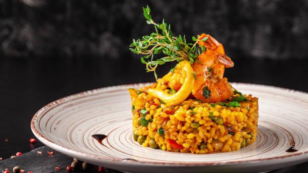 het concept van de spaanse keuken. paella met zeevruchten, garnalen, inktvis en groenen. mooi bedienen in het restaurant. - paella stockfoto's en -beelden