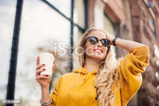 870648602 istock photo The concept of street fashion. young stylish girl student wearing boyfrend jeans, white sneakers bright yellow sweatshirt.She holds coffee to go. portrait of smiling girl in sunglasses 870648598