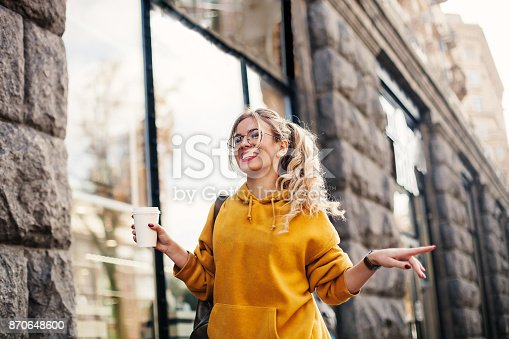 870648602 istock photo The concept of street fashion. young stylish girl student wearing boyfrend jeans, white sneakers bright yellow sweetshot.She holds coffee to go and dance . portrait of smiling girl in glasses 870648600