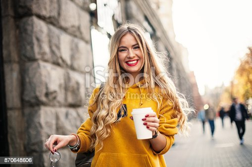 870648602 istock photo The concept of street fashion. young stylish girl student wearing boyfrend jeans, white sneakers bright yellow sweetshot.She holds coffee to go. portrait of smiling girl in sunglasses and with bag posing in the street 870648606
