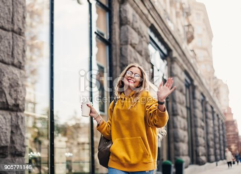 870648602 istock photo The concept of street fashion. young stylish girl student wearing boyfrend jeans, white sneakers bright yellow sweetshot.She holds coffee to go and dance . portrait of smiling girl in glasses 905771146