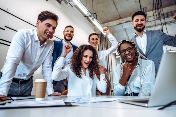 The concept of success. A group of young business people learned good news their project was approved in the work. Company development and joy. stock photo