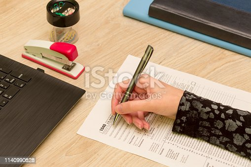 Woman filling 1040 individual income tax return form in office.
