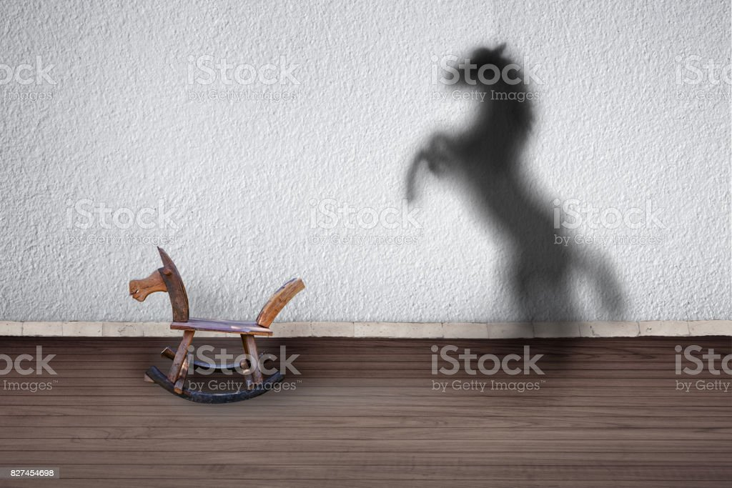 The concept of the hidden potencial.Toy horse in the room which casts a shadow on the wall. stock photo