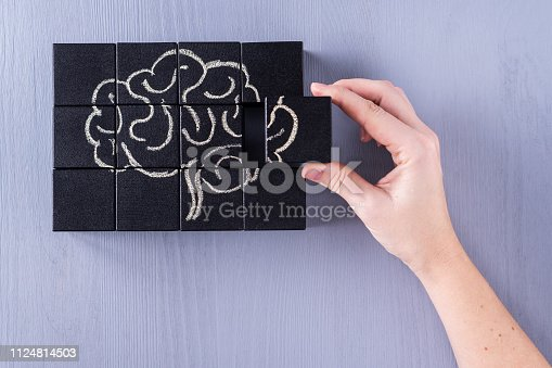 585087100istockphoto The concept of the human brain. Education, science and medical concept.  Brain drawn in chalk on black cubes. 1124814503