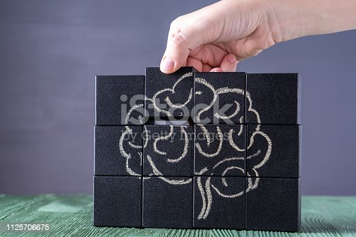 585087100istockphoto The concept of the human brain. Education, science and medical concept.  Brain drawn in chalk on black cubes. 1125706675