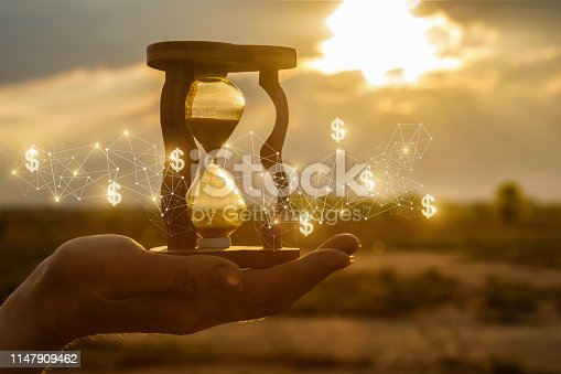 The concept of time and the new financial ideas. Hourglass in hand with and financial structure at sunset.