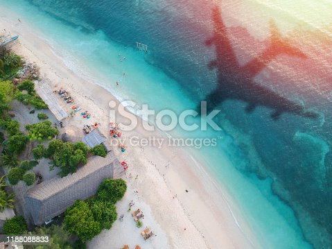 1058205304 istock photo The concept of travel and air travel. Top view of the sandy coast of the ocean, with the shadow on the water from the landing plane. Light 1188088833