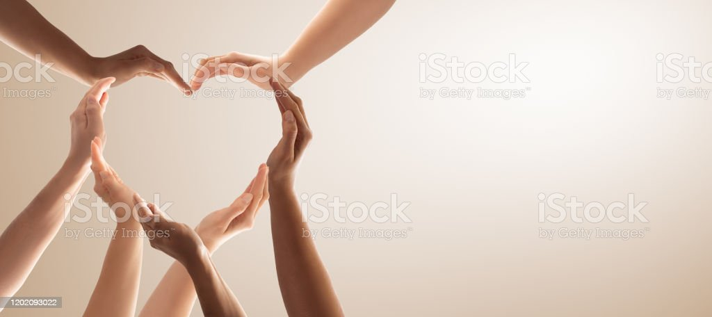 The concept of unity, cooperation, teamwork and charity. Symbol and shape of heart created from hands.The concept of unity, cooperation, partnership, teamwork and charity. A Helping Hand Stock Photo