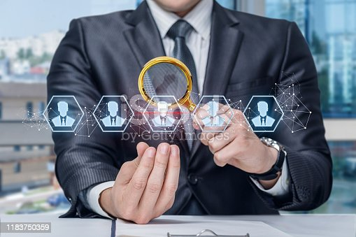 The concept of working with human resource. The Manager considers the icons of the workers through a magnifying glass.