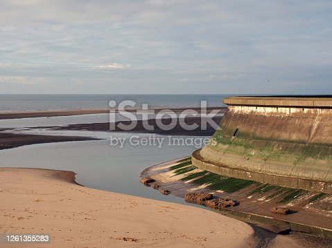 the concrete seawall of the old boating pool at blackpool lancashire surrounded by pools of water on the beach at low tide with a blue sea and clouds
